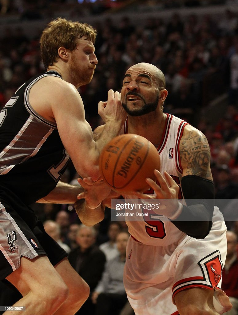 Carlos Boozer #5 of the Chicago Bulls is hit in the face by Matt Bonner #15 of the San Antonio Spurs at the United Center on February 17, 2011 in Chicago, Illinois. The Bulls defeated the Spurs 109-99.