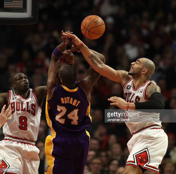 Carlos Boozer of the Chicago Bulls knocks the ball away from Kobe Bryant of the Los Angeles Lakers as Luol Deng also defends at the United Center on...