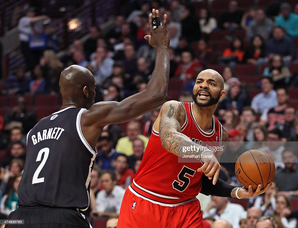 Carlos Boozer #5 of the Chicago Bulls looks to pass against Kevin Garnett #2 of the Brooklyn Nets at the United Center on February 13, 2014 in Chicago, Illinois. The Bulls defeated the Nets 92-76.