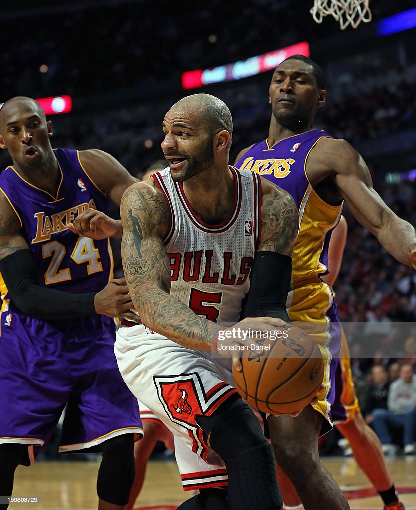 Carlos Boozer #5 of the Chicago Bulls looks to pass under pressure from Kobe Bryant #24 and Metta World Peace #15 of the Los Angeles Lakers at the United Center on January 21, 2013 in Chicago, Illinois. The Bulls defeated the Lakers 95-83.