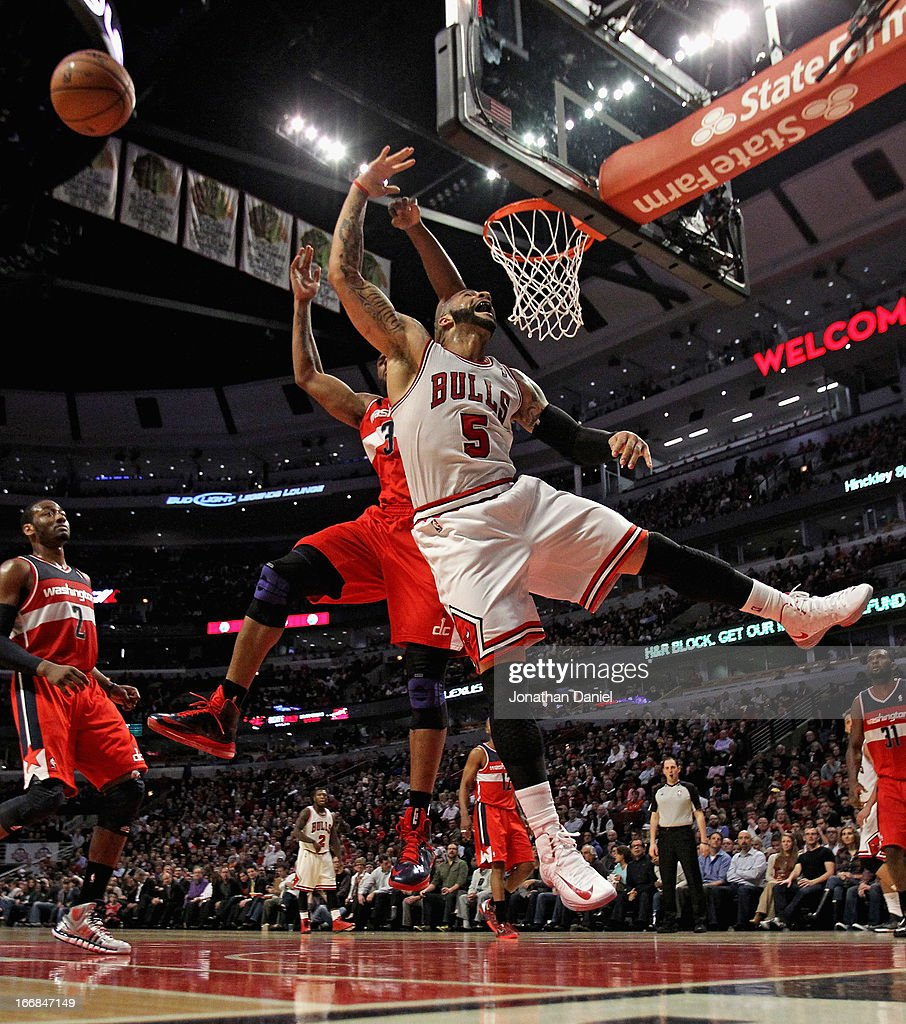 <a gi-track='captionPersonalityLinkClicked' href=/galleries/search?phrase=Carlos+Boozer&family=editorial&specificpeople=201638 ng-click='$event.stopPropagation()'>Carlos Boozer</a> #5 of the Chicago Bulls looses the ball after being fouled by <a gi-track='captionPersonalityLinkClicked' href=/galleries/search?phrase=Trevor+Booker&family=editorial&specificpeople=4123563 ng-click='$event.stopPropagation()'>Trevor Booker</a> #35 of the Washington Wizards at the United Center on April 17, 2013 in Chicago, Illinois. The Bulls defeated the Wizards 95-92.