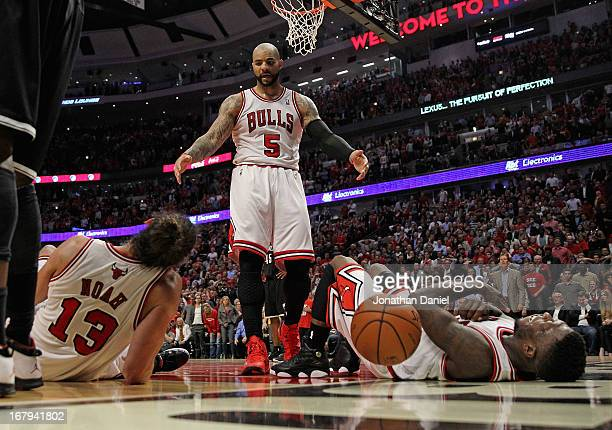 Carlos Boozer of the Chicago Bulls moves to help up teammates Joakim Noah and Nate Robinson after a play against the Brooklyn Nets in Game Six of the...