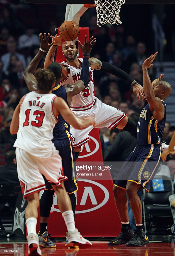 Carlos Boozer #5 of the Chicago Bulls passes the ball to Joakim Noah #13 between Roy Hibbert #55 (L) and Davis West #21 of the Indiana Pacers at the United Center on December 4, 2012 in Chicago, Illinois. The Pacers defeated the Bulls 80-76.