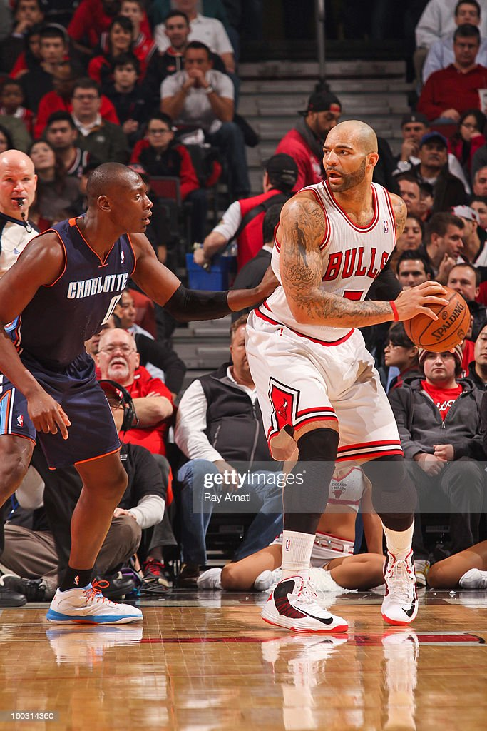 Carlos Boozer #5 of the Chicago Bulls posts up against Bismack Biyombo #0 of the Charlotte Bobcats on January 28, 2013 at the United Center in Chicago, Illinois.