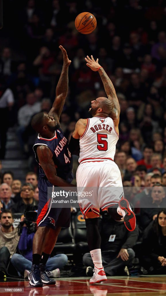 Carlos Boozer #5 of the Chicago Bulls puts up a shot over Ivan Johnson #44 of the Atlanta Hawks at the United Center on January 14, 2013 in Chicago, Illinois.
