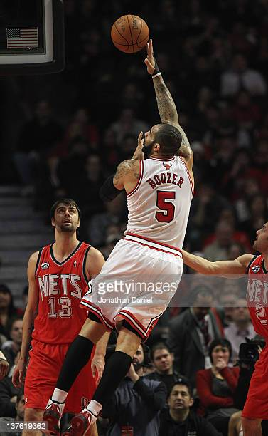 Carlos Boozer of the Chicago Bulls puts up a shot over Mehmet Okur of the New Jersey Nets at the United Center on January 23 2012 in Chicago Illinois...