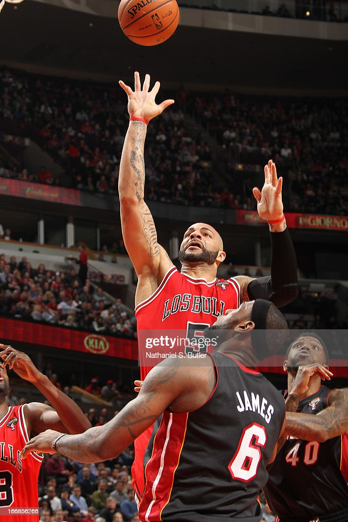 <a gi-track='captionPersonalityLinkClicked' href=/galleries/search?phrase=Carlos+Boozer&family=editorial&specificpeople=201638 ng-click='$event.stopPropagation()'>Carlos Boozer</a> #5 of the Chicago Bulls puts up the shot against <a gi-track='captionPersonalityLinkClicked' href=/galleries/search?phrase=LeBron+James&family=editorial&specificpeople=201474 ng-click='$event.stopPropagation()'>LeBron James</a> #6 of the Miami Heat Chicago Bulls on March 27, 2013 at the United Center in Chicago, Illinois.