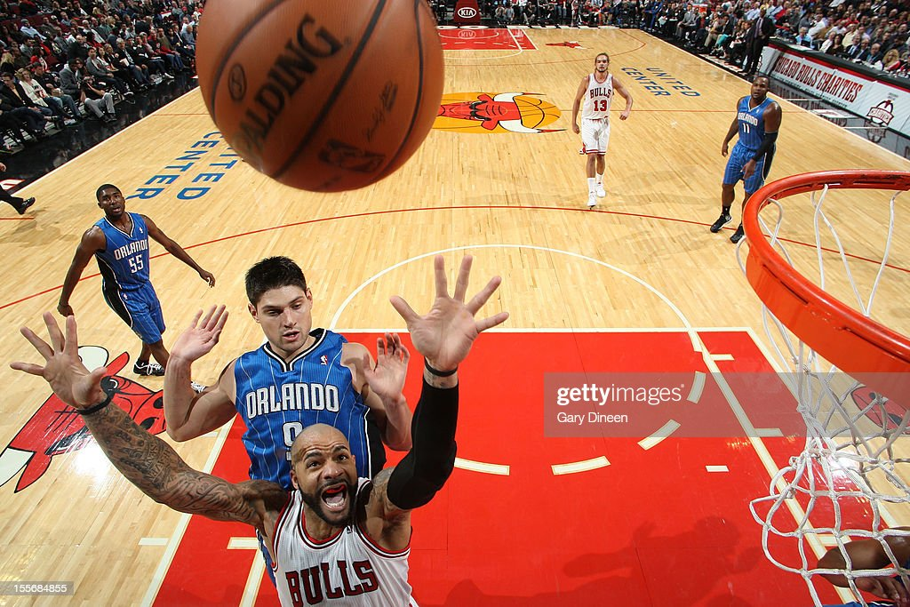 <a gi-track='captionPersonalityLinkClicked' href=/galleries/search?phrase=Carlos+Boozer&family=editorial&specificpeople=201638 ng-click='$event.stopPropagation()'>Carlos Boozer</a> #5 of the Chicago Bulls reaches for a rebound against Nikola Vucevic #9 of the Orlando Magic during the NBA game on November 6, 2012 at the United Center in Chicago, Illinois.