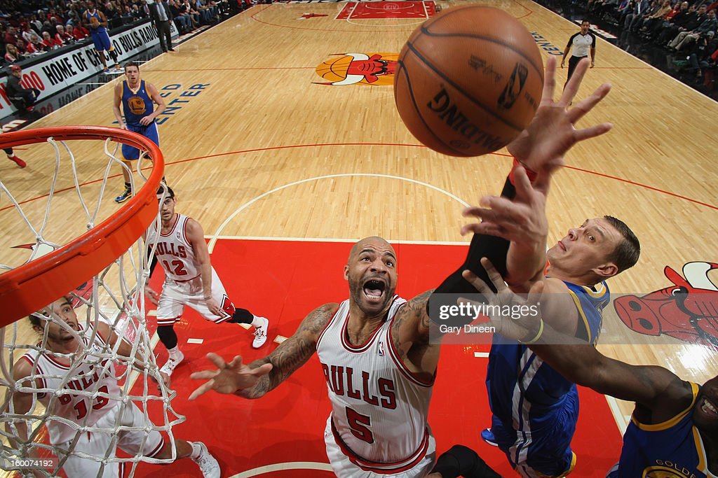 Carlos Boozer #5 of the Chicago Bulls reaches for a rebound against Andris Biedrins #15 of the Golden State Warriors on January 25, 2012 at the United Center in Chicago, Illinois.