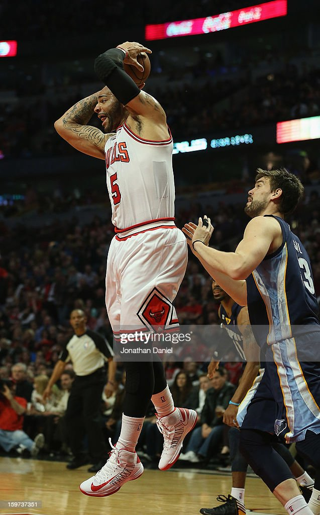 Carlos Boozer #5 of the Chicago Bulls rebounds in front of Marc Gasol #33 of the Memphis Grizzles at the United Center on January 19, 2013 in Chicago, Illinois.