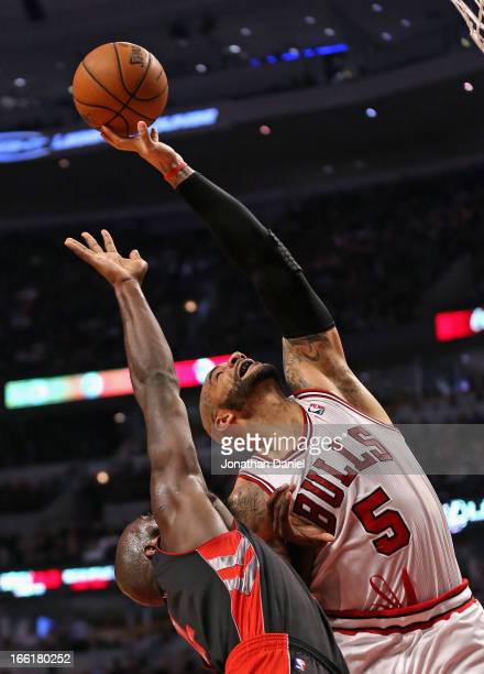 Carlos Boozer of the Chicago Bulls rebounds over Quincy Acy of the Toronto Raptors at the United Center on April 9 2013 in Chicago Illinois NOTE TO...