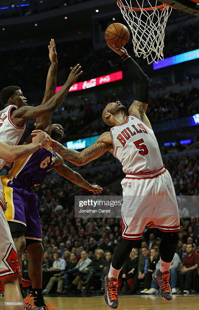 <a gi-track='captionPersonalityLinkClicked' href=/galleries/search?phrase=Carlos+Boozer&family=editorial&specificpeople=201638 ng-click='$event.stopPropagation()'>Carlos Boozer</a> #5 of the Chicago Bulls rebounds over teammate <a gi-track='captionPersonalityLinkClicked' href=/galleries/search?phrase=Jimmy+Butler+-+Basketball&family=editorial&specificpeople=9860567 ng-click='$event.stopPropagation()'>Jimmy Butler</a> #21 and Earl Clark #6 of the Los Angeles Lakers at the United Center on January 21, 2013 in Chicago, Illinois. The Bulls defeated the Lakers 95-83.