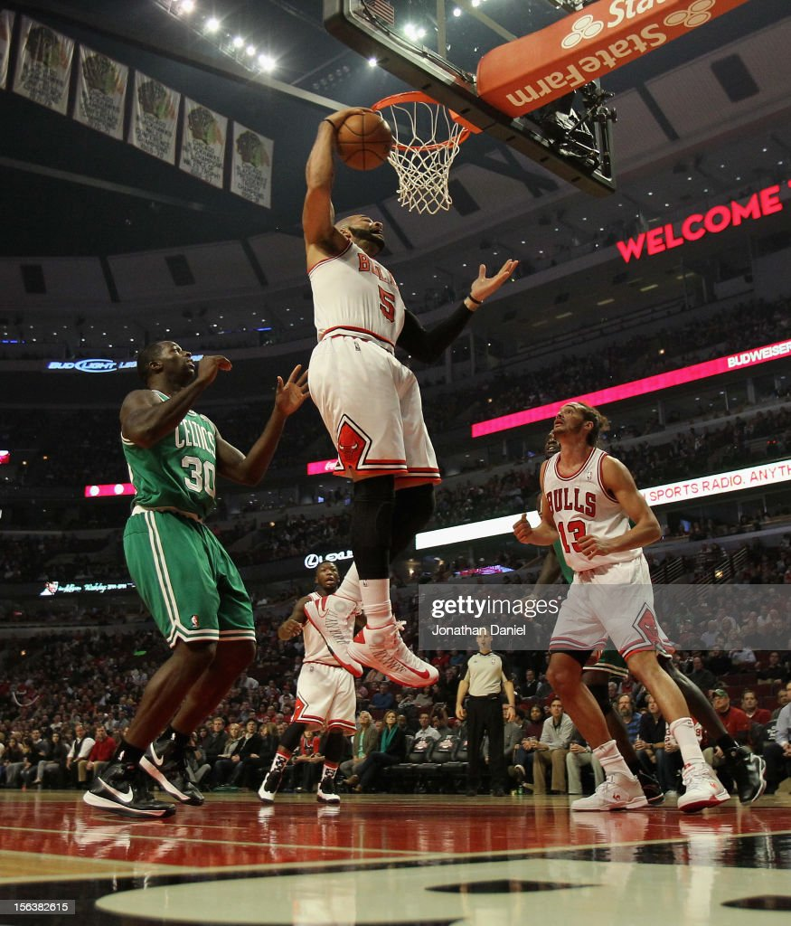 Carlos Boozer #5 of the Chicago Bulls rebounds over teammate Joakim Noah #13 and Brandon Bass #30 of the Boston Celtics at the United Center on November 12, 2012 in Chicago, Illinois. The Celtics defeated the Bulls 101-95.