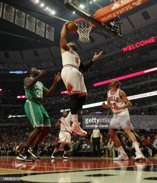 Carlos Boozer of the Chicago Bulls rebounds over teammate Joakim Noah and Brandon Bass of the Boston Celtics at the United Center on November 12 2012...