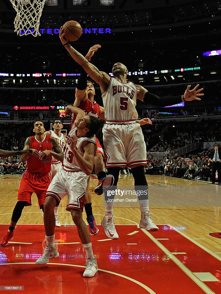 Carlos Boozer #5 of the Chicago Bulls rebounds over teammate Joakim Noah #13 and Blake Griffin #32 of the Los Angeles Clippers at the United Center on December 11, 2012 in Chicago, Illinois. The Clippers defeated the Bulls 94-89.