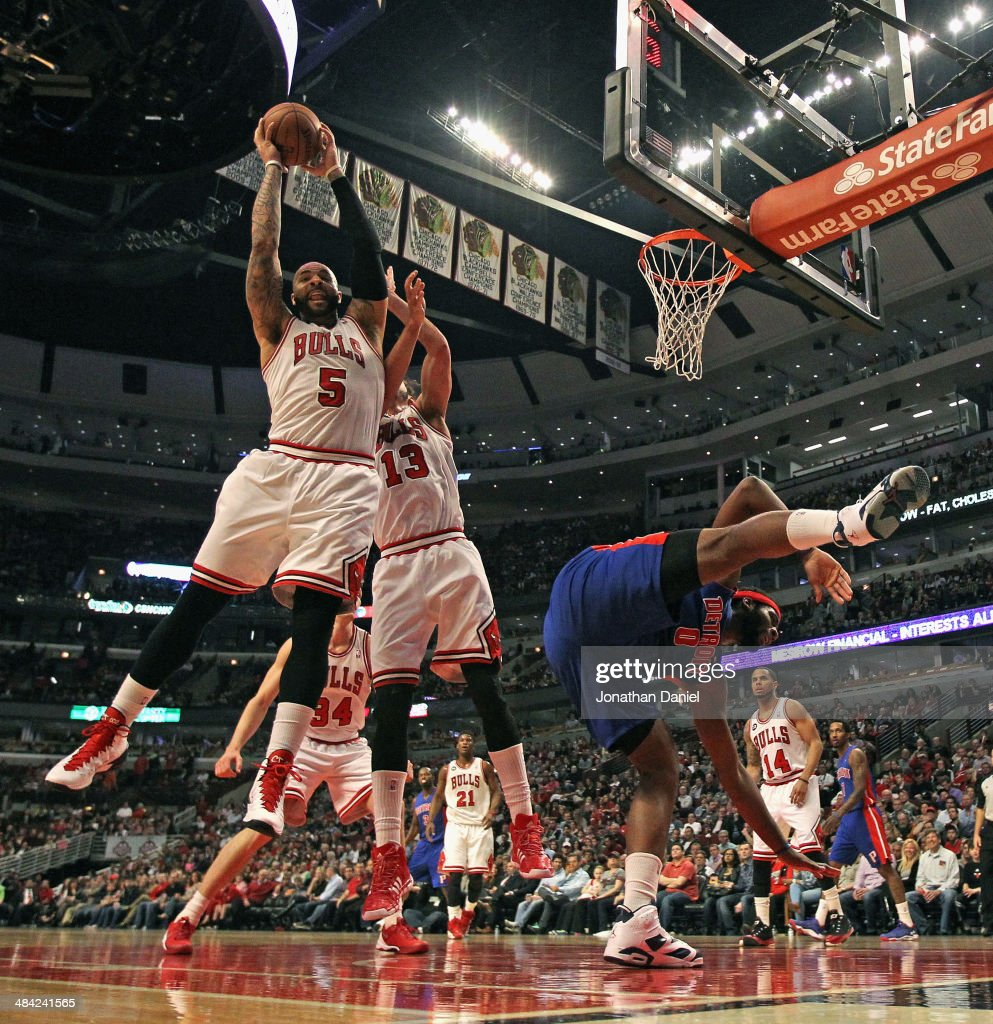 Carlos Boozer #5 of the Chicago Bulls rebounds over teammate Joakim Noah #13 as Andre Drummond #0 of the Detroit Pistons looses his balance at the United Center on April 11, 2014 in Chicago, Illinois.
