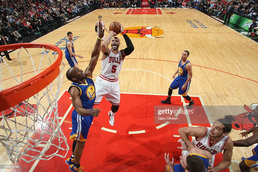 Carlos Boozer #5 of the Chicago Bulls shoots against Carl Landry #7 of the Golden State Warriors on January 25, 2012 at the United Center in Chicago, Illinois.