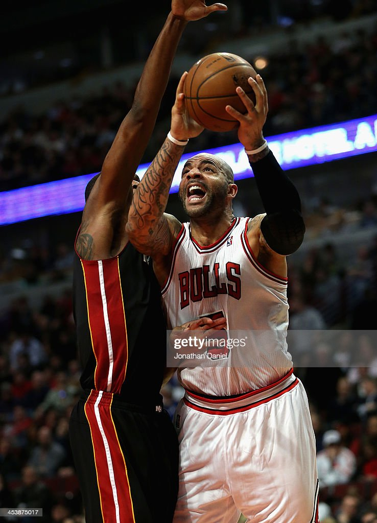 <a gi-track='captionPersonalityLinkClicked' href=/galleries/search?phrase=Carlos+Boozer&family=editorial&specificpeople=201638 ng-click='$event.stopPropagation()'>Carlos Boozer</a> #5 of the Chicago Bulls shoots against <a gi-track='captionPersonalityLinkClicked' href=/galleries/search?phrase=Chris+Bosh&family=editorial&specificpeople=201574 ng-click='$event.stopPropagation()'>Chris Bosh</a> #1 of the Miami Heat on his way to a game-high 27 points at the United Center on December 5, 2013 in Chicago, Illinois. The Bulls defeated the Heat 107-87.