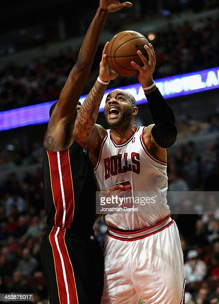 Carlos Boozer of the Chicago Bulls shoots against Chris Bosh of the Miami Heat on his way to a gamehigh 27 points at the United Center on December 5...