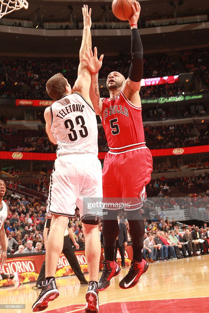 Carlos Boozer #5 of the Chicago Bulls shoots against Mirza Teletovic #33 of the Brooklyn Nets on March 2, 2013 at the United Center in Chicago, Illinois.