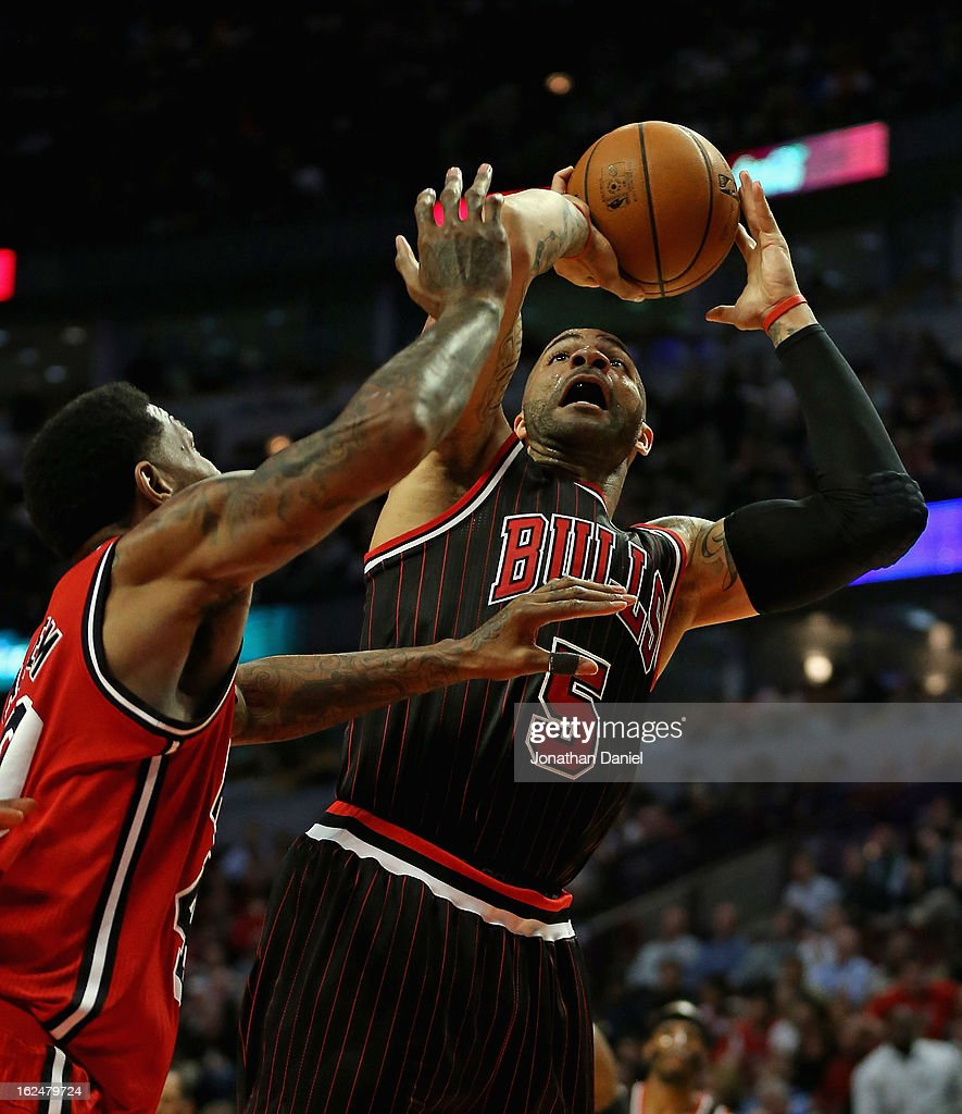 Carlos Boozer #5 of the Chicago Bulls shoots against Udonis Haslem #40 of the Miami Heat at the United Center on February 21, 2013 in Chicago, Illinois. The Heat defeated the Bulls 86-67.