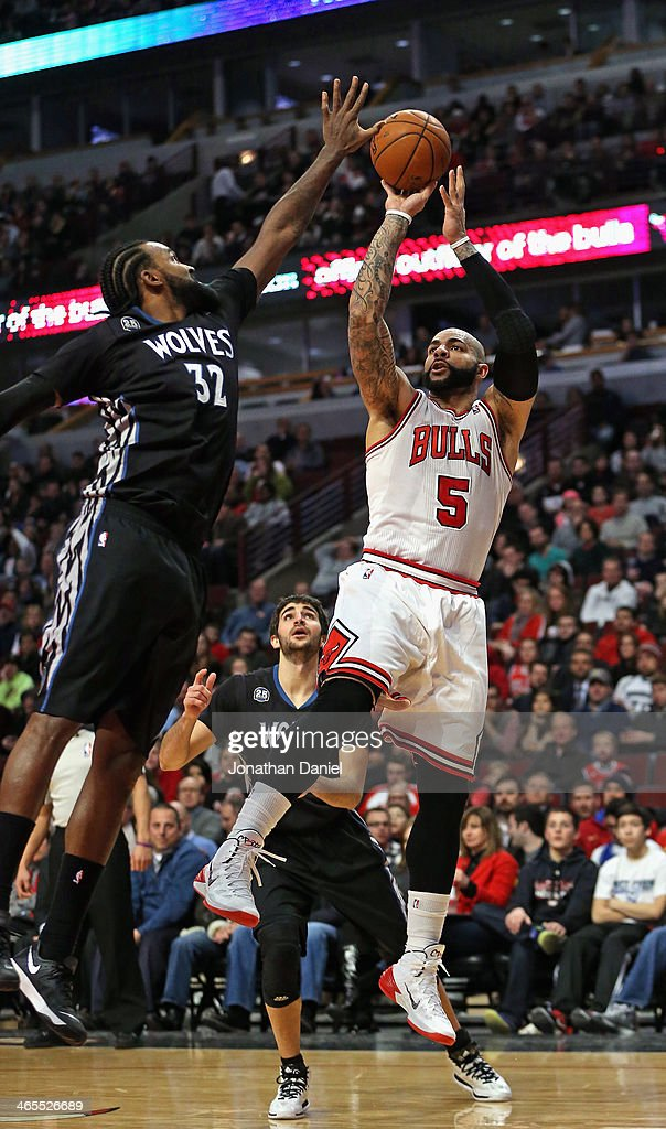 Carlos Boozer #5 of the Chicago Bulls shoots over Ronny Turiaf #32 of the Minnesota Timberwolves at the United Center on January 27, 2014 in Chicago, Illinois. The Timberwolves defeated the Bulls 95-86.