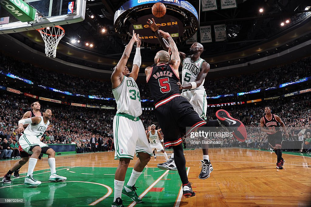 Carlos Boozer #5 of the Chicago Bulls shoots the ball against Paul Pierce #34 and Kevin Garnett #5 of the Boston Celtics on January 18, 2013 at the TD Garden in Boston, Massachusetts.