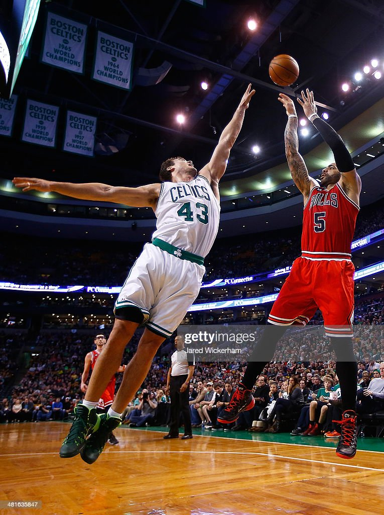 Carlos Boozer #5 of the Chicago Bulls takes a shot over Kris Humphries #43 of the Boston Celtics in the second half during the game at TD Garden on March 30, 2014 in Boston, Massachusetts.