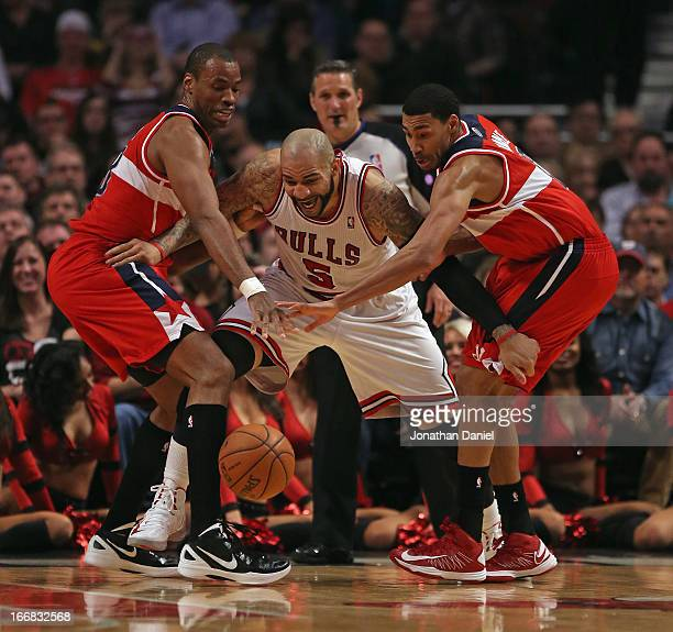 Carlos Boozer of the Chicago Bulls tries to recapture the ball under pressure from Jason Collins and Garrett Temple of the Washington Wizards at the...