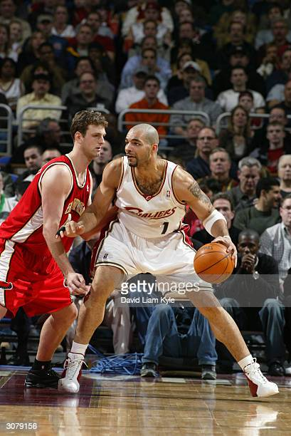 Carlos Boozer of the Cleveland Cavaliers is defended by Chris Crawford of the Atlanta Hawks during the game at Gund Arena on March 3 2004 in...