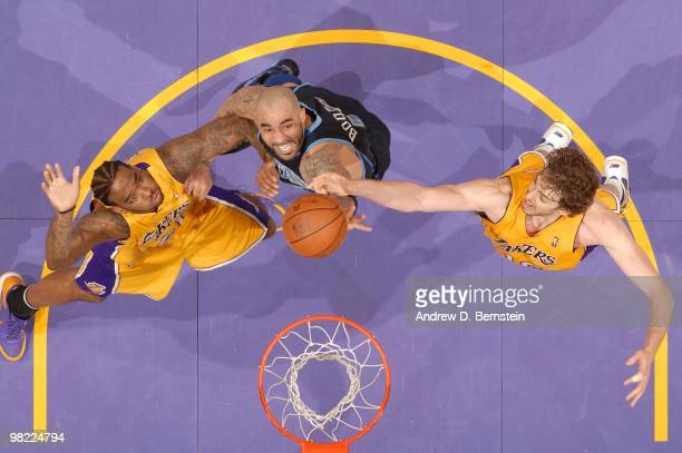Carlos Boozer of the Utah Jazz reaches for a rebound between Josh Powell and Pau Gasol of the Los Angeles Lakers at Staples Center on April 2 2010 in...