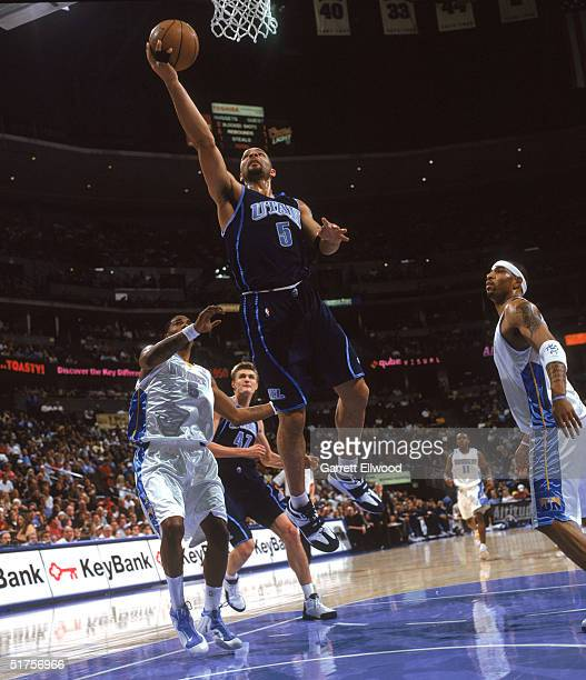 Carlos Boozer of the Utah Jazz shoots against Kenyon Martin and Andrei Kirilenko of the Denver Nuggets during the game at Pepsi Center on November 4...