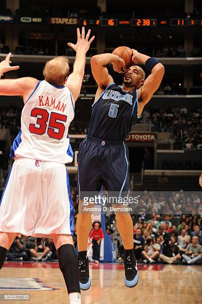 Carlos Boozer of the Utah Jazz shoots over Chris Kaman of the Los Angeles Clippers at Staples Center on November 3 2008 in Los Angeles California...