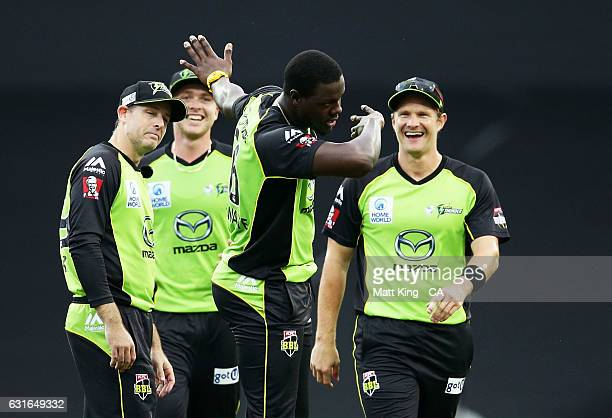 Carlos Brathwaite of the Thunder celebrates with team mates after taking the wicket of Johan Botha of the Sixers during the Big Bash League match...