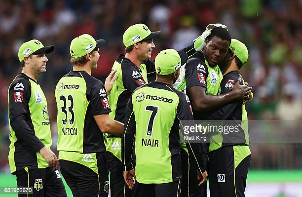 Carlos Brathwaite of the Thunder celebrates with team mates after taking the wicket of Tim Ludeman of the Strikers during the Big Bash League match...
