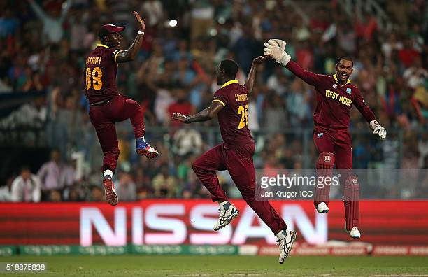 Carlos Brathwaite of the West Indies celebrates the wicket of Joe Root of England with Darren Sammy Captain of the West Indies and Denesh Ramdin...