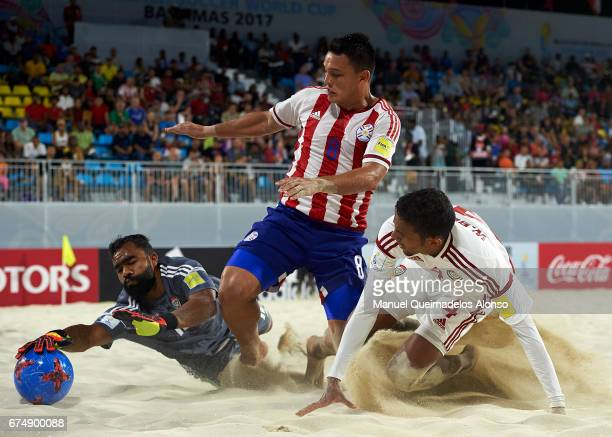 Carlos Carballo of Paraguay competes for the ball with goalkeeper Humaid Jamal and Waleed Beshr of United Arab Emirates during the FIFA Beach Soccer...