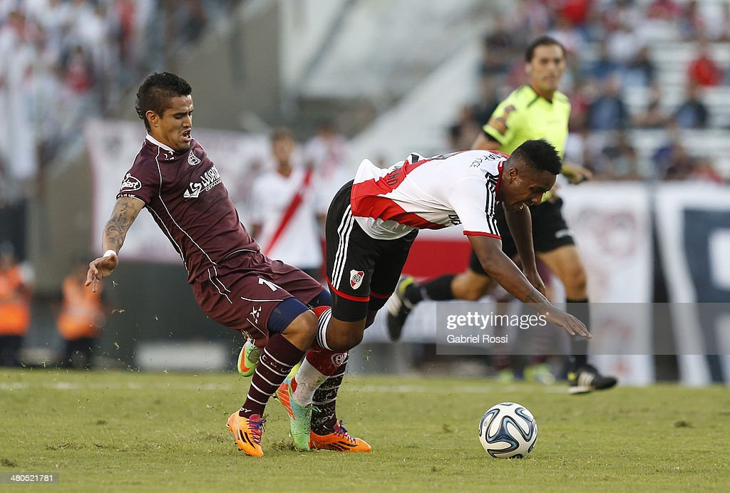 Carlos Carbonero of River Plate recieves a foul from Victor Ayala of Lanus during a match between River Plate and Lanus as part of ninth round of Torneo Final 2014 at Monumental Antonio Vespucio Liberti Stadium on March 23, 2014 in Buenos Aires, Argentina.