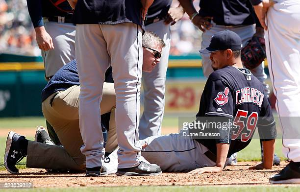 Carlos Carrasco of the Cleveland Indians is attended to by trainer James Quinlan after injuring his left leg making an out on Andrew Romine of the...