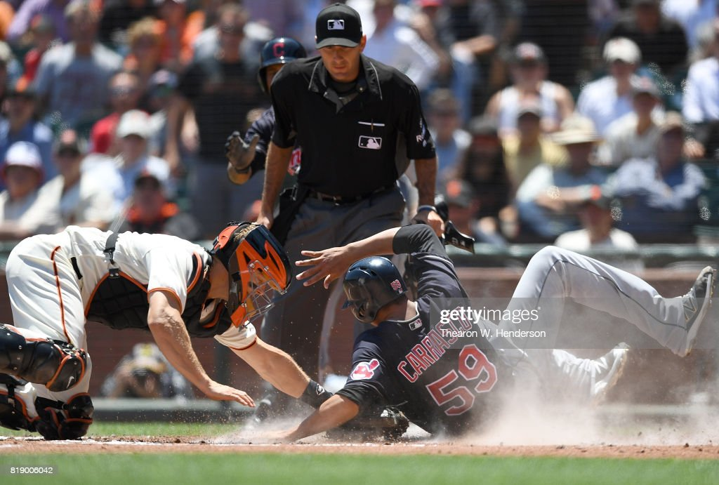 Carlos Carrasco #59 of the Cleveland Indians scores sliding around the tag of Nick Hundley #5 of the San Francisco Giants in the top of the third inning at AT&T Park on July 19, 2017 in San Francisco, California.