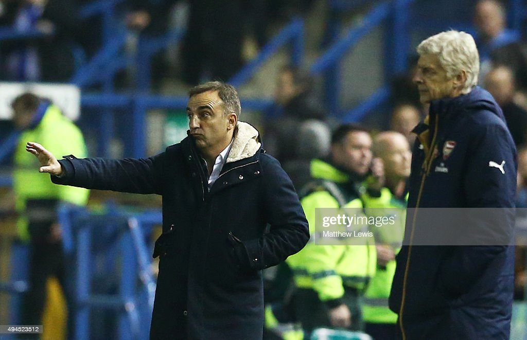 Carlos Carvalhal the manager of Sheffield Wednesday gesrures as Arsene Wenger the manager of Arsenal looks on during the Capital One Cup fourth round match between Sheffield Wednesday and Arsenal at Hillsborough Stadium on October 27, 2015 in Sheffield, England.