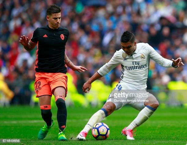 Carlos Casemiro of Real Madrid CF competes for the ball with Santi Mina of Valencia CF during the La Liga match between Real Madrid CF and Valencia...