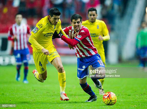 Carlos Castro of Real Sporting de Gijon duels for the ball with Vicente Gomez of UD Las Plamas during the La Liga match between Real Sporting de...