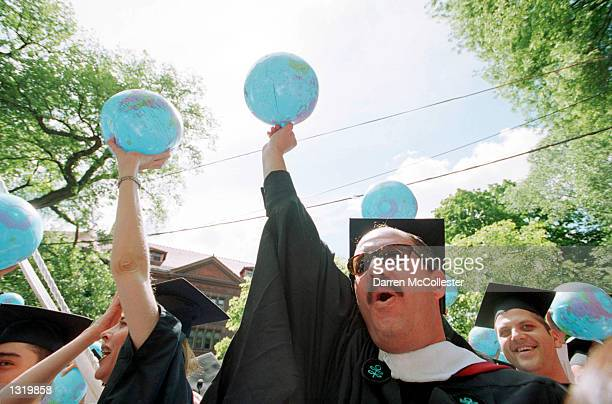 Carlos ChavezTaffur of Peru raises a plastic globe after receiving his degree from the school of Government at Harvard University June 7 2001 during...