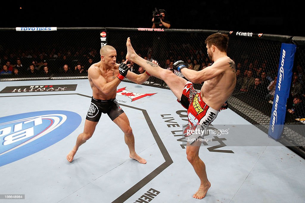 Carlos Condit (R) attempts a kick against Georges St-Pierre in their welterweight title bout during UFC 154 on November 17, 2012 at the Bell Centre in Montreal, Canada.