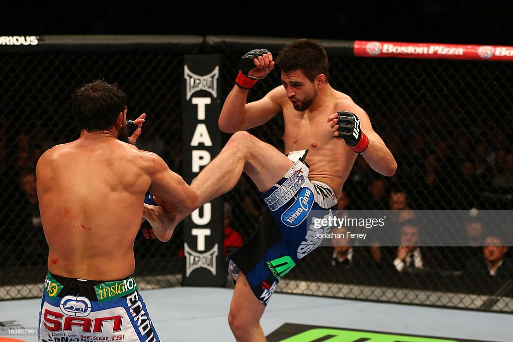 Carlos Condit kicks Johny Hendricks in their welterweight bout during the UFC 158 event at Bell Centre on March 16, 2013 in Montreal, Quebec, Canada.