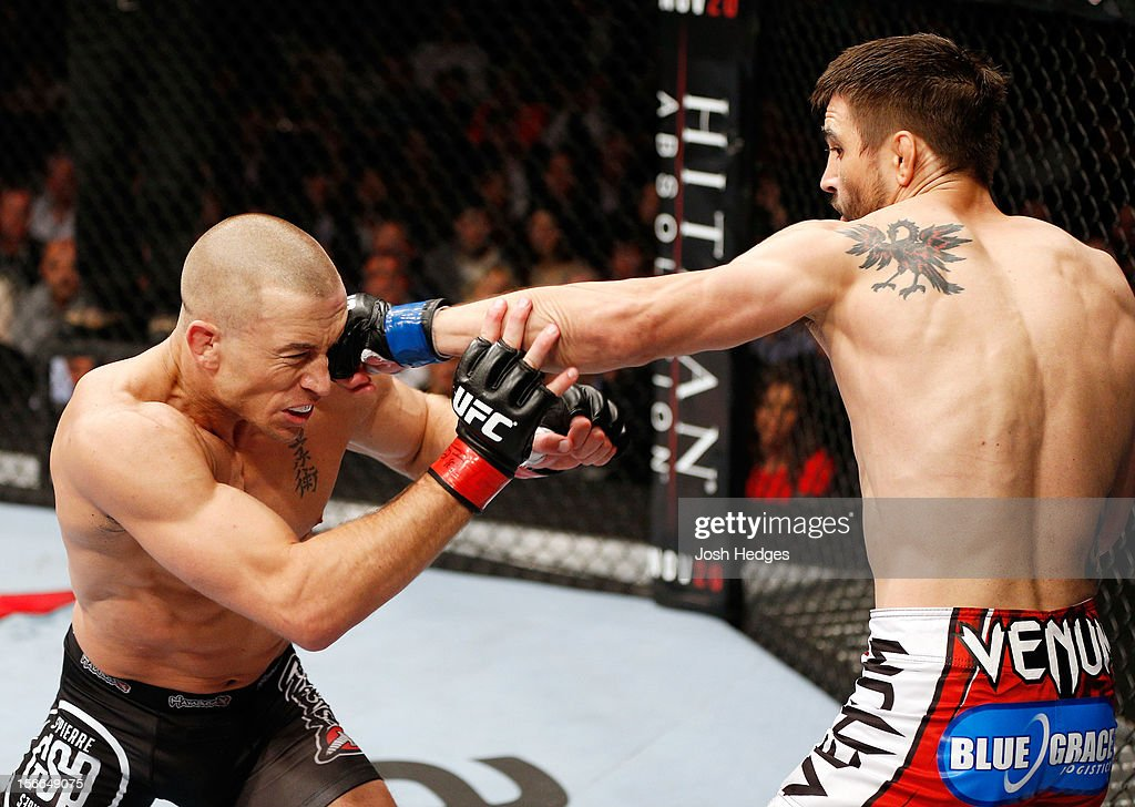 Carlos Condit (R) lands a punch against Georges St-Pierre in their welterweight title bout during UFC 154 on November 17, 2012 at the Bell Centre in Montreal, Canada.