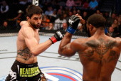 Carlos Condit punches Tyron Woodley in their welterweight bout at UFC 171 inside American Airlines Center on March 15 2014 in Dallas Texas