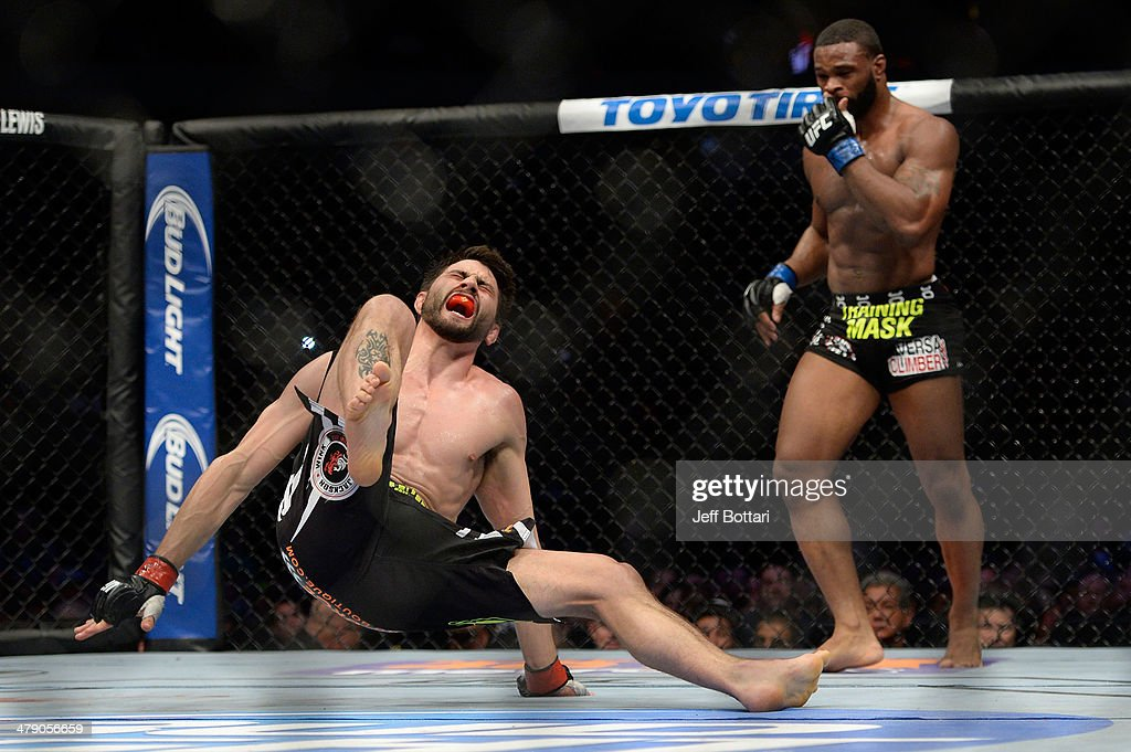 Carlos Condit screams as he falls after being kicked by Tyron Woodley in their welterweight fight during the UFC 171 event inside American Airlines...
