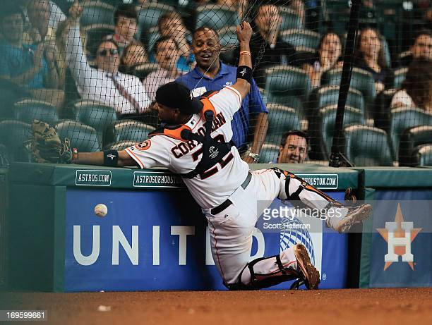 Carlos Corporan of the Houston Astros fails to catch a baseball behind home plate in the seventh inning against the Colorado Rockies at Minute Maid...
